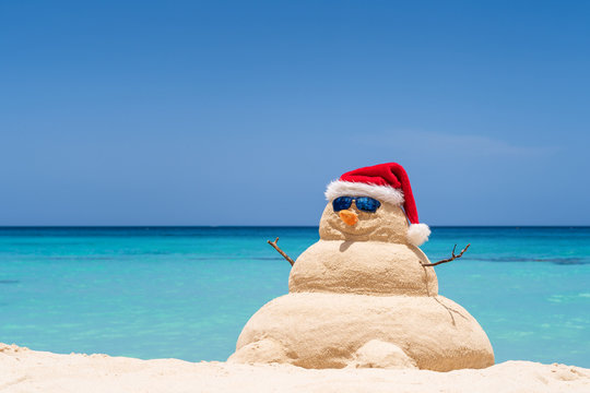 Smiling sandy snowman with red santa hat on the caribbean beach. Holiday concept for New Year and Christmas Cards