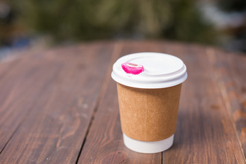 Pink lipstick marks left on disposable coffee cup