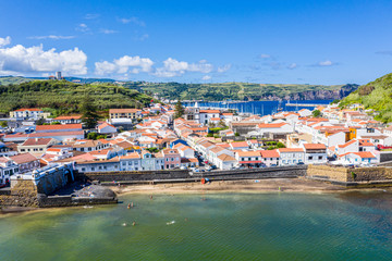 Idyllic beach Praia and azure bay Baia do Porto Pim. Fortifications, walls, gates, red roofs of historical touristic Horta town centre, yachts in the port, Faial island, Azores, Portugal, Europe
