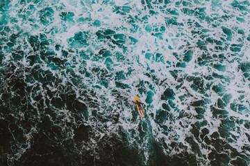 Aerial shot of surfers doing surf at sunset time. picture provided with drone. Concept about nature and sport