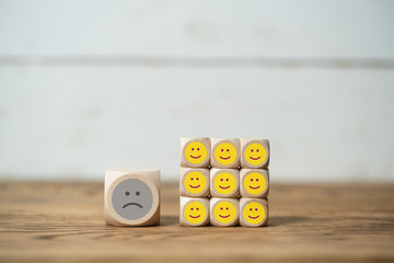 cubes with emoticons on wooden background