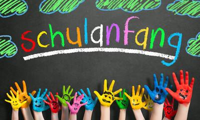 """viele angemalte Kinderhände mit Smileys vor Kreidetafel mit dem Wort """"Schulanfang"""""""