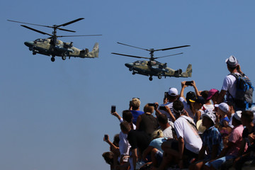 People take pictures as Russian military helicopters fly during the Navy Day parade in the Black Sea port of Sevastopol