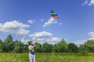 Cute white kid playing colorful kite outdoor at countyrside landscape. Color photo of boy isolated at sunny blue sky background.