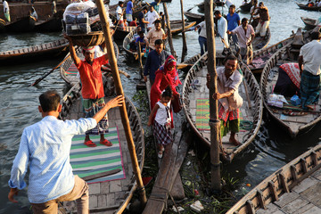 People gather at a boat terminal to cross the Buriganga river by boat in Dhaka