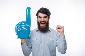 Portrait of a cheerful excited  man with a foam finger shouting and looking at camera
