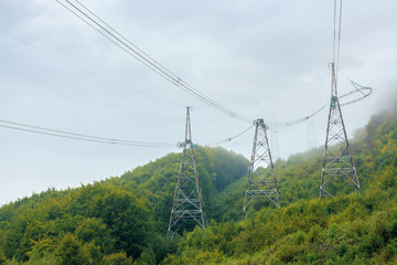 high voltage power lines tower in mountains.  energy delivery background. efficient electricity delivery concept. hazy weather with overcast sky