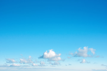 fleecy clouds on an azure sky. beautiful nature background. dynamic side lit cloudscape