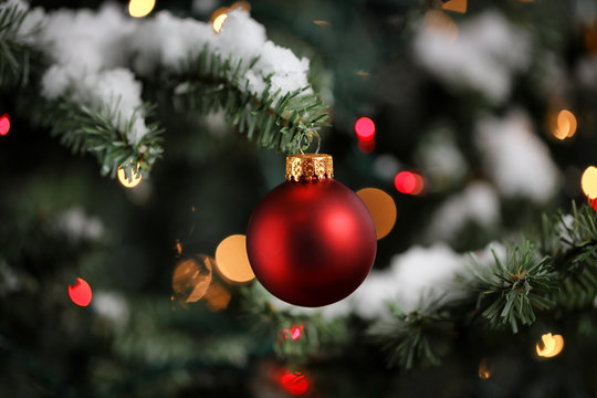 Traditional artificial Christmas tree with red ball ornament with glowing lights and snow in background