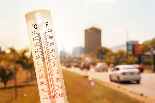 Thermometer in front of an urban scene during heatwave
