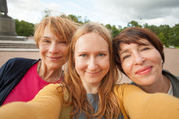 Three diverse happy women friends making selfie photo and having fun outdoors