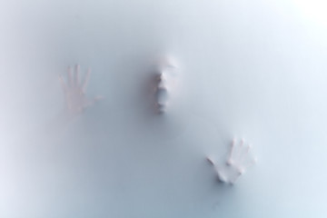 man's face with wide open mouth and raised hands, standing behind the fabric, glass wall,man asking help as the muder is killing him, white and black photo. Fototapete