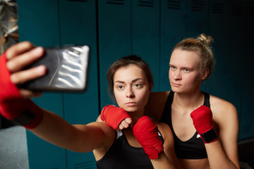 Portrait of two female fighters taking selfie in changing room before boxing practice, copy space