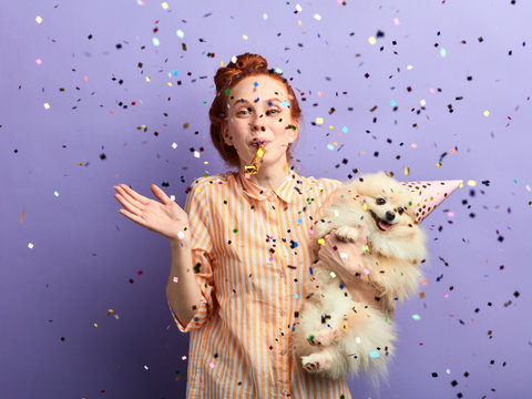 crazy girl and her adorable dog having fun in the studio. close up portrait, isolated blue background, studio shot.