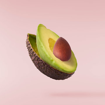 Fresh ripe avocado with leaves falling in the air.