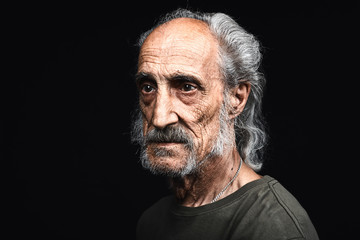 sad tired old man with many wrinkles on his face waiting for death. close up side view photo. isolated black background. studio shot.copy space