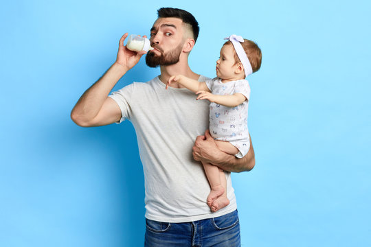 Young crazy father checking milk before giving it to kid. close up photo. isolated blue background. studio shot.funny greedy daddy drinking from the baby's bottle.