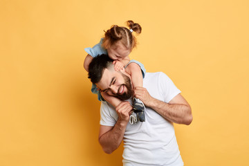 little girl wants dad's attention, beautiful funny girl tickling her elder brother while sitting on his shoulders. close up photo. isolated yellow background. feeling , emotion, kid bites her father