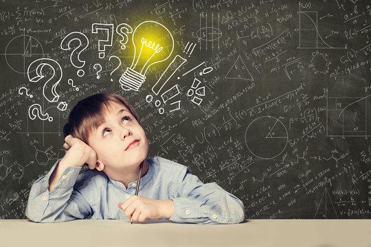 Idea! Smart kid student with lightbulb on blackboard