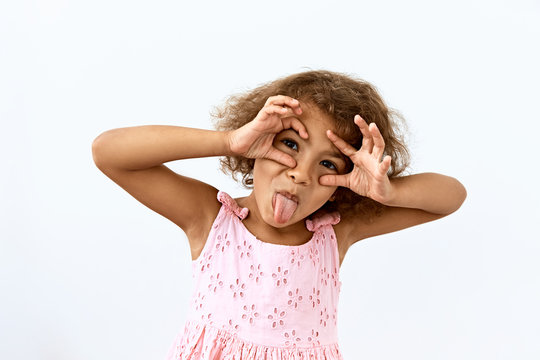 Making face,funny  foolishes portrait of little African American girl, against white background.