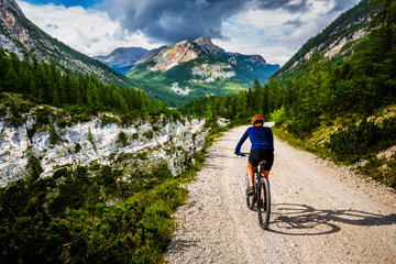 Wall Mural - Tourist cycling in Cortina d'Ampezzo, stunning rocky mountains on the background. Woman riding MTB enduro flow trail. South Tyrol province of Italy, Dolomites.