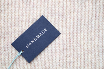 Label with inscription Handmade on knitted texture background