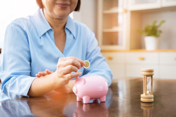 hand putting coin money to piggy bank saving, Close up of Old Asian woman smiling putting a coin inside piggy bank as investment.