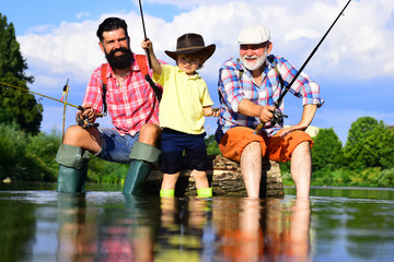 Generations men. Man with his son and father on river fishing with fishing rods. Grandpa and grandson are fly fishing on river.