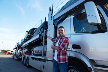 Middle aged trucker in front of truck trailer with cars. Transporting cars to the market. Wall mural