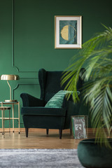 Golden lamp on elegant table next to dark green velvet armchair