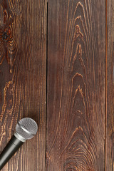 Microphone on wooden background, top view. Dynamic microphone on brown wooden table with copy space, vertical image.