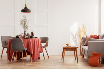 Living and dining room interior with grey couch and table covered with orange tablecloth Fototapete