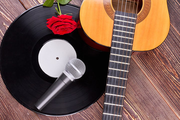 Musical objects and flower on wooden background. Guitar, vinyl record, microphone and red rose. Music still life.