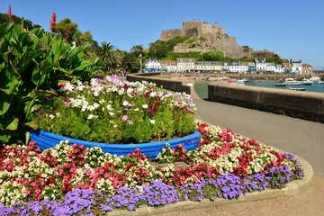 Jersey, U.K. July 28th 2019, 12th century Grouville landmark Mont Orguiel castle and harbour with a promenade of park gardens.