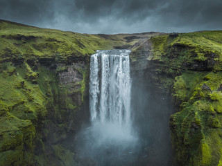 Skogafoss waterfall Iceland. Beautiful huge waterfall surrounded by green hills. Spring in Iceland.