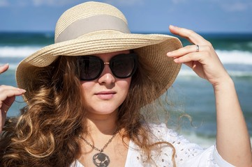 Young elegant Caucasian lady in a straw hat with sunglasses at the seaside. Protection from the sun concept image.