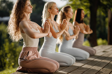 Four young girls are practising yoga sitting  on the wooden podium in the garden with folded hands near the chest