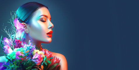Sexy brunette model girl with bouquet of beautiful flowers. Beauty young woman with bunch of flowers in colorful neon lights. Art design