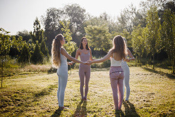 Four young women are practising yoga  in the open air standing in a circle with closed eyes in the nature on the sunny day