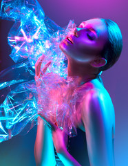 Fashion model woman in colorful bright neon lights posing in studio through transparent film. Portrait of beautiful sexy girl in UV. Art design colorful makeup