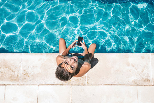 Young teenager boy sitting on edge of pool using mobile phone