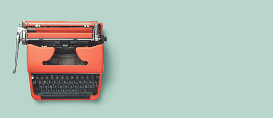retro banner or header image with red vintage 60s / 70s typewriter on a bright turquoise background, top view, copyspace for your text
