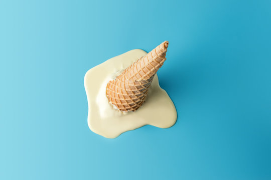 Melted ice cream with ice cream cone on pastel blue background. Minimal summer food concept.