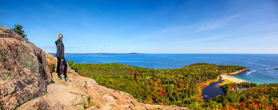 Female hiker standing on ledge enjoying view of water from Beehive Trail in Acadia National Park