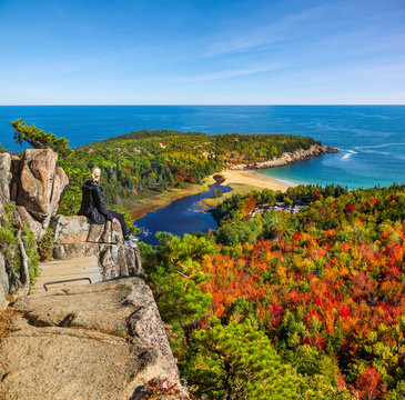 Female hiker sitting on ledge enjoying view of water from Beehive Trail in Acadia National Park