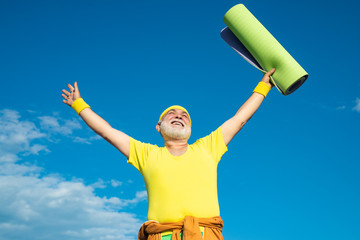 Cheerful aged men holding yoga mats. Happy Senior sport man is doing sport outdoors.