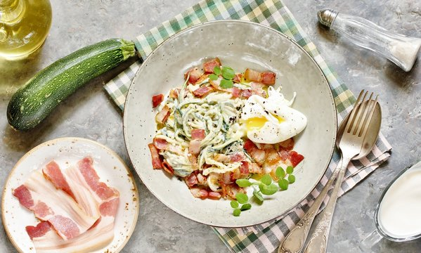Low-Carb keto carbonara pasta with spaghetti (noodles) of zucchini with cream, fried bacon and poached egg. decorated with pea sprouts. in a beautiful light dish. top view