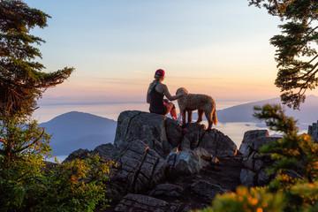Foto auf Gartenposter Beige Adventurous Girl is hiking with a dog on top of St. Mark's Mountain during a sunny summer sunset. Located in West Vancouver, British Columbia, Canada.