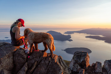 Adventurous Girl is hiking with a dog on top of St. Mark's Mountain during a sunny summer sunset. Located in West Vancouver, British Columbia, Canada.