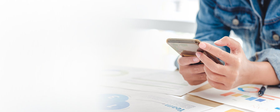 close up creative director designer use mobile phone at table with data sheet at office when planning work.banner space for display of design or text